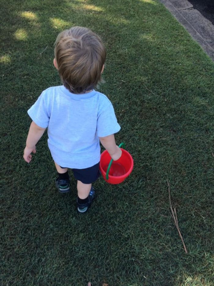 Toddler walking on grass with plastic bucket